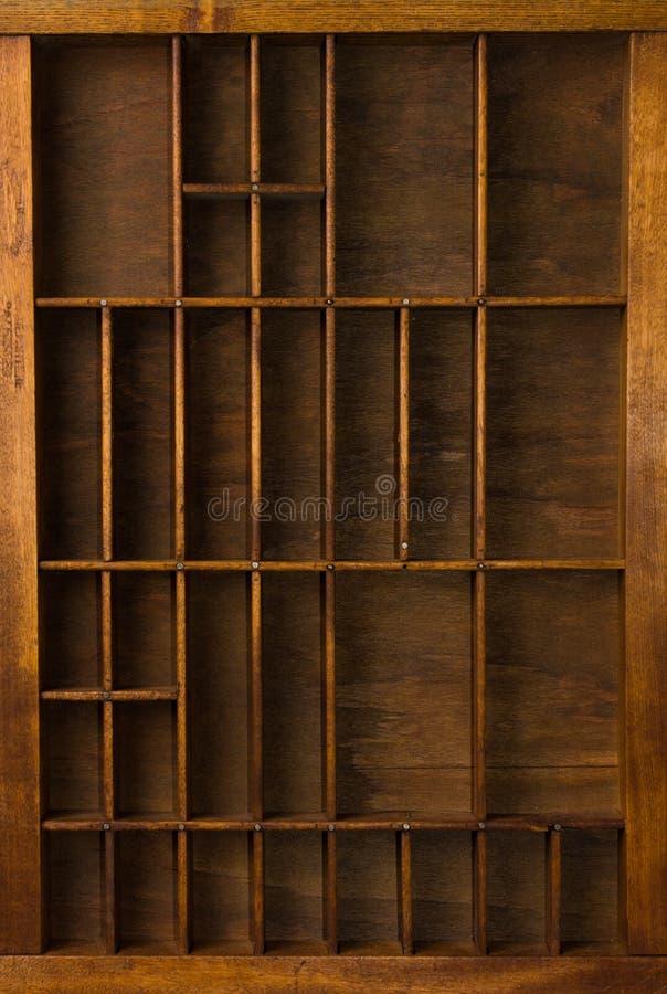 Il cassetto antico del compositore con i divisori si chiude sulla vista superiore fotografia stock