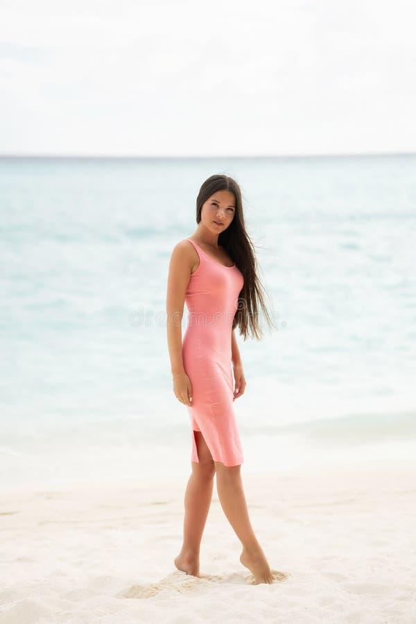 Il castana in un vestito adatto rosa cammina su una spiaggia bianca come la neve immagine stock libera da diritti