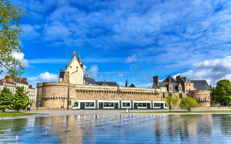 Il castello dei duchi di Bretagna, un tram della città e l'acqua rispecchiano la fontana a Nantes, Francia immagine stock