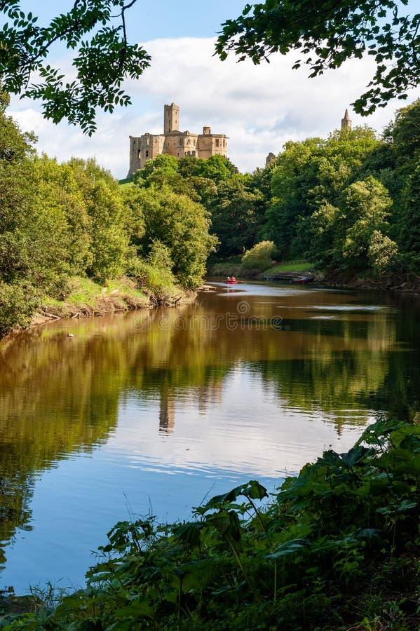 Il castello di Warkworth si riflette nel fiume Coquet, Morpeth, Northumberland, Regno Unito immagini stock