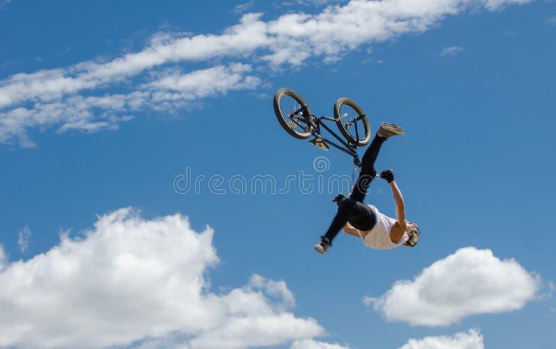 Il cavaliere di BMX che eseguono i trucchi ed i salti sopra una rampa a Sydney Park ciclano il centro con il fondo del cielo blu fotografia stock