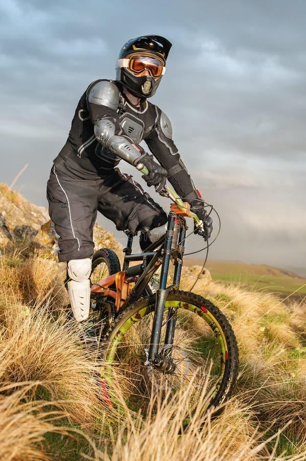Il cavaliere in discesa su un mountain bike in un mountain bike guida lungo la strada in natura contro il contesto della montagna immagini stock libere da diritti