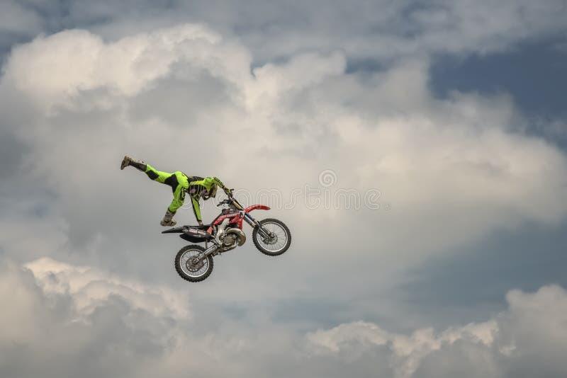 Il cavaliere professionale di freestyle motocross effettua un trucco in un salto con il motociclo su fondo del cielo blu della nu fotografia stock libera da diritti