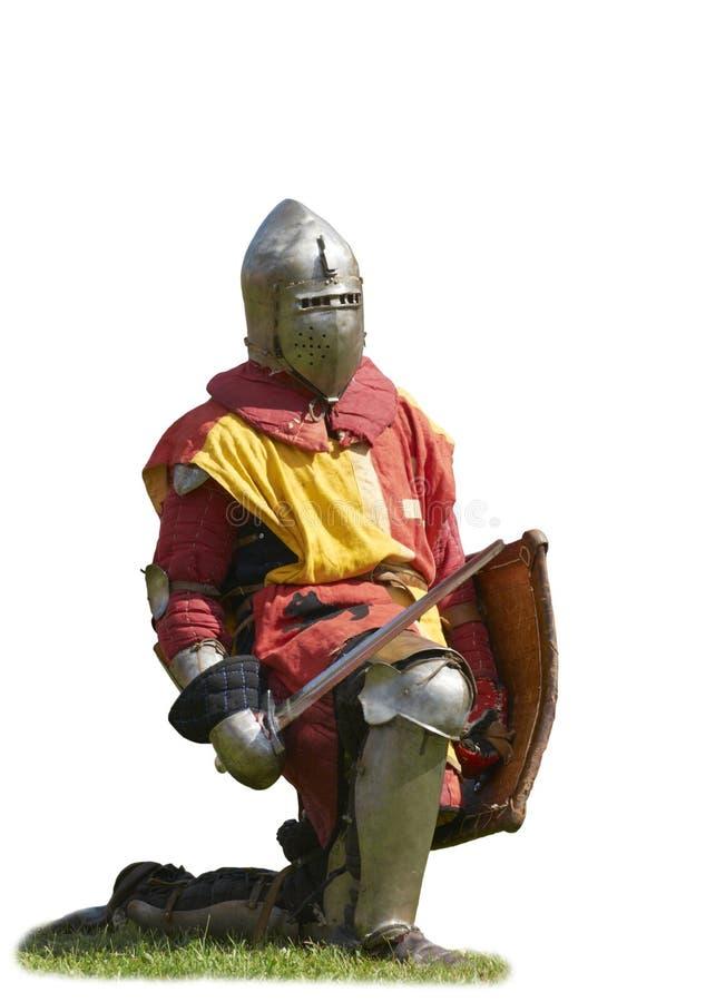 Il cavaliere in un'armatura, levantesi in piedi su un ginocchio fotografia stock libera da diritti