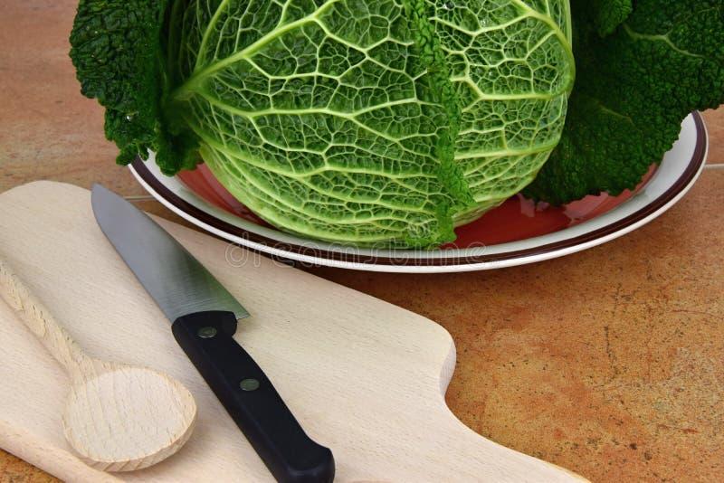 Il cavolo su un piatto sul tagliere della cucina è un coltello e un cucchiaio fotografie stock libere da diritti