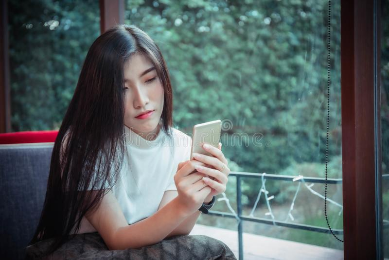 Il cellulare di tenuta della bella ragazza dell'asiatico ed avere telefono cellulare di sguardo felice di emozione immagine stock libera da diritti