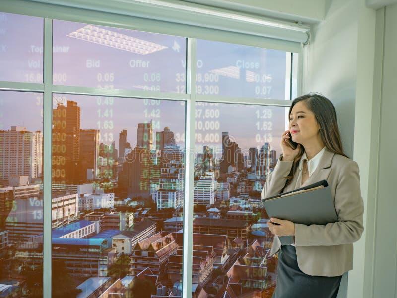 Il cellulare moderno di uso delle donne di affari parla del wh del mercato azionario fotografia stock