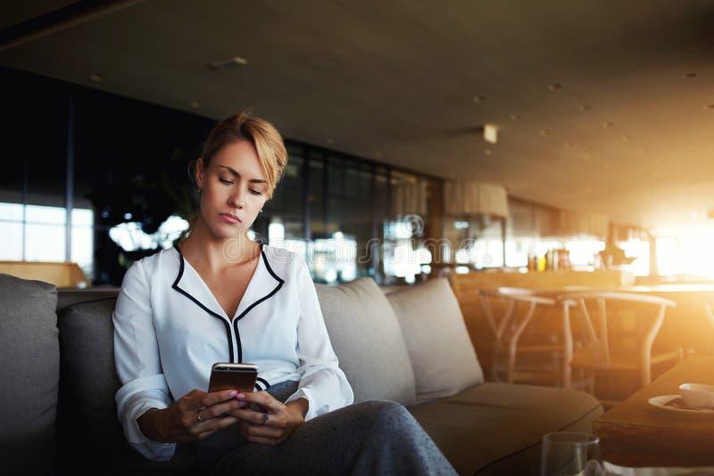 Il CEO fiero della giovane donna sta utilizzando il telefono cellulare, mentre sta aspettando i partner in ristorante durante il  fotografia stock