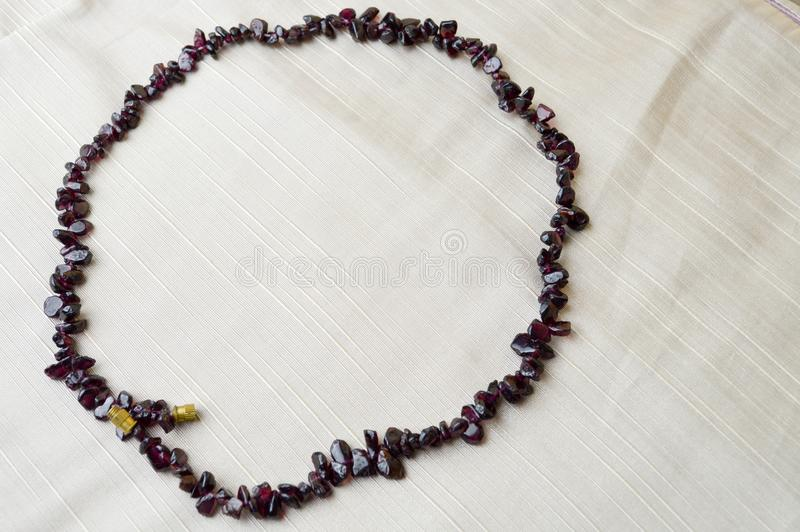 Il cerchio è fatto di belle perle femminili, collane delle pietre scure marroni, ambrate con un fondo di tessuto beige fotografia stock