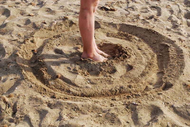 Il cerchio attinge la sabbia con i piedi sul centro fotografia stock libera da diritti
