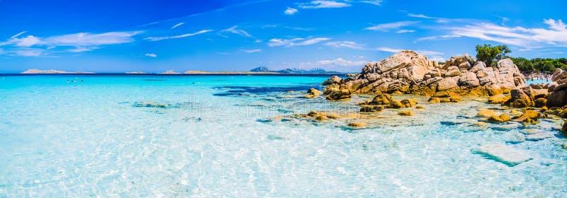 Il chiaro azzurro stupefacente ha colorato l'acqua di mare con le rocce del gtanote in spiaggia di Capriccioli, Sardegna, Italia fotografie stock libere da diritti