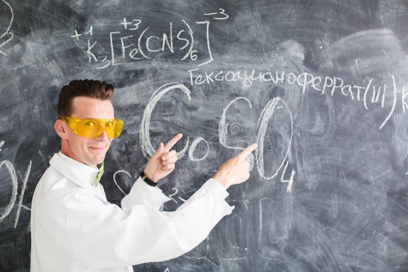 Il chimico scrive una formula chimica sulla lavagna immagini stock