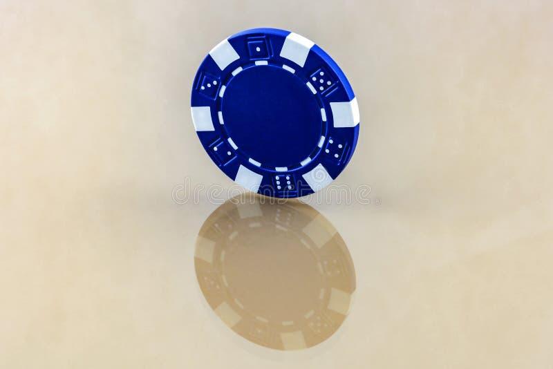 Il chip blu del casinò sta sulla superficie riflettente immagini stock