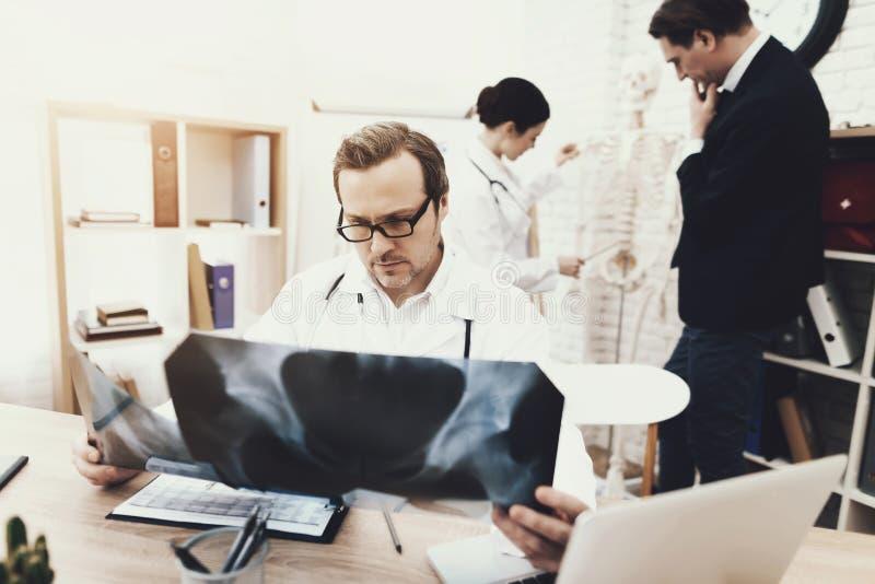 Il chirurgo con esperienza con lo stetoscopio diagnostica il paziente che esamina i raggi x immagine stock libera da diritti