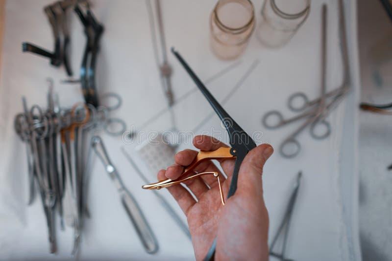 Il chirurgo di medico tiene in sua mano una clip medica nera per realizzare un'operazione immagini stock