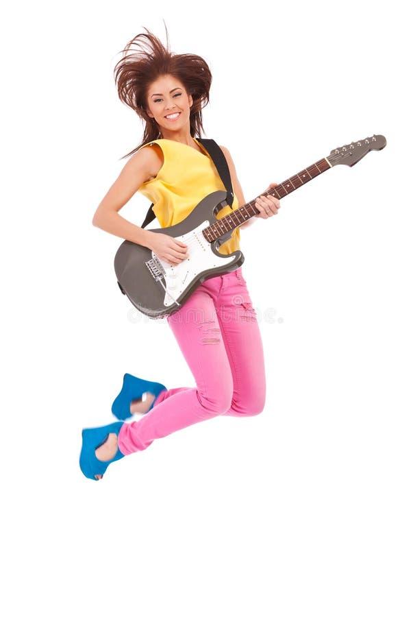 Il chitarrista appassionato della donna salta nell'aria immagini stock libere da diritti