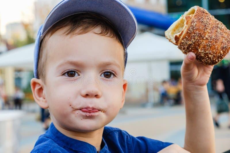 Il cibo del rotolo ? un piacere reale per il ragazzo Fine settimana, bambino in parco fotografia stock