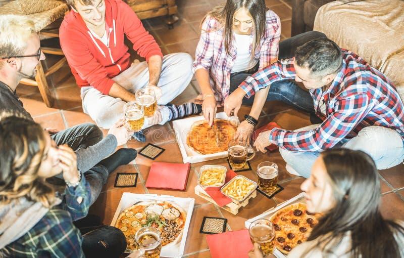 Il cibo felice degli amici porta via la pizza a casa dopo lavoro - concetto di amicizia con i giovani che godono insieme del temp fotografia stock