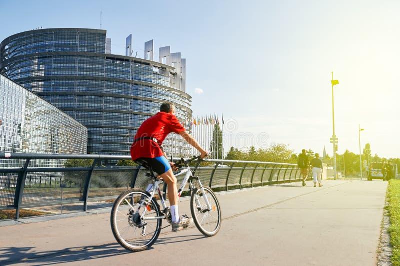 Il ciclismo Strasburgo allegra dell'uomo senior, il Parlamento Europeo costruisce immagini stock