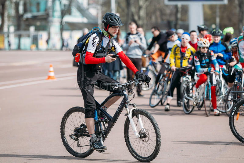Il ciclista del giovane in abiti sportivi per il riciclaggio usa il fon dello smartphone fotografia stock