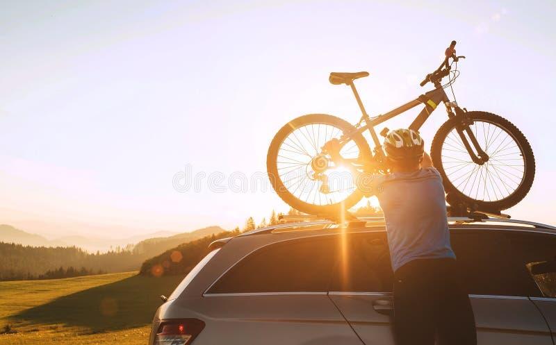 Il ciclista dell'uomo veared in vestiti di riciclaggio ed in casco protettivo installa il suo mountain bike sul tetto dell'automo immagini stock libere da diritti