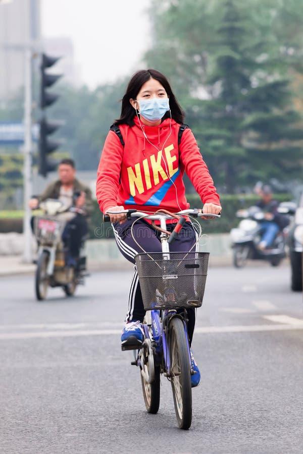 il ciclista femminile Fronte-mascherato in smog ha ricoperto la città, Pechino, Cina immagini stock libere da diritti