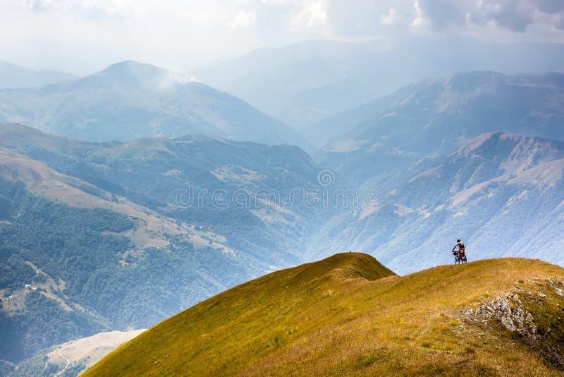 Il ciclista in mountain-bike sta viaggiando negli altopiani della regione di Tusheti, immagini stock