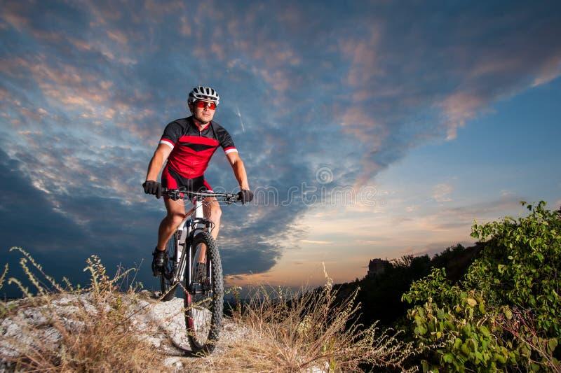 Il ciclista sul mountain bike corre in discesa nella natura fotografia stock libera da diritti