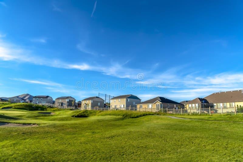 Il cielo blu radiante e si rannuvola le case ed il campo da golf un giorno soleggiato immagine stock libera da diritti
