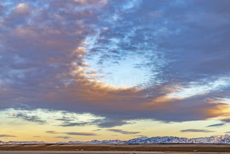 Il cielo della sfuocatura riempito di grigio gonfio si rannuvola una valle e la neve ha ricoperto la montagna immagini stock