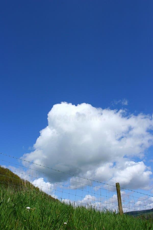 Il cielo, le nubi e la barriera del filo fotografia stock