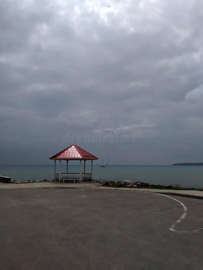 Il cielo si appanna il rilassamento della spiaggia sabbiosa del lago water scenico fotografia stock