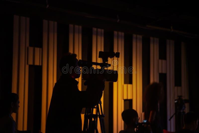 Il cineoperatore sta lavorando nello studio durante la fucilazione immagini stock