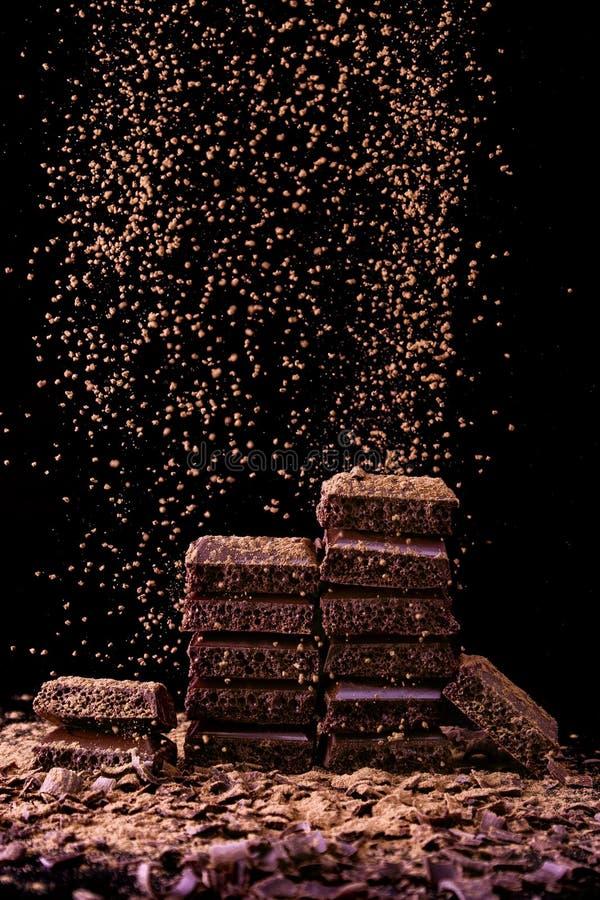 Il cioccolato collega con i pori su fondo scuro con cacao in polvere fotografia stock