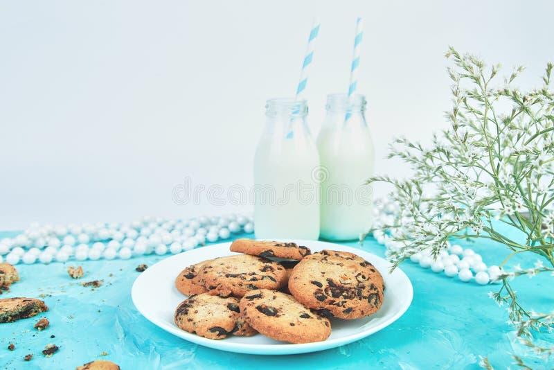 Il cioccolato del biscotto con bottiglie per il latte organiche si avvicina al fiore fotografia stock