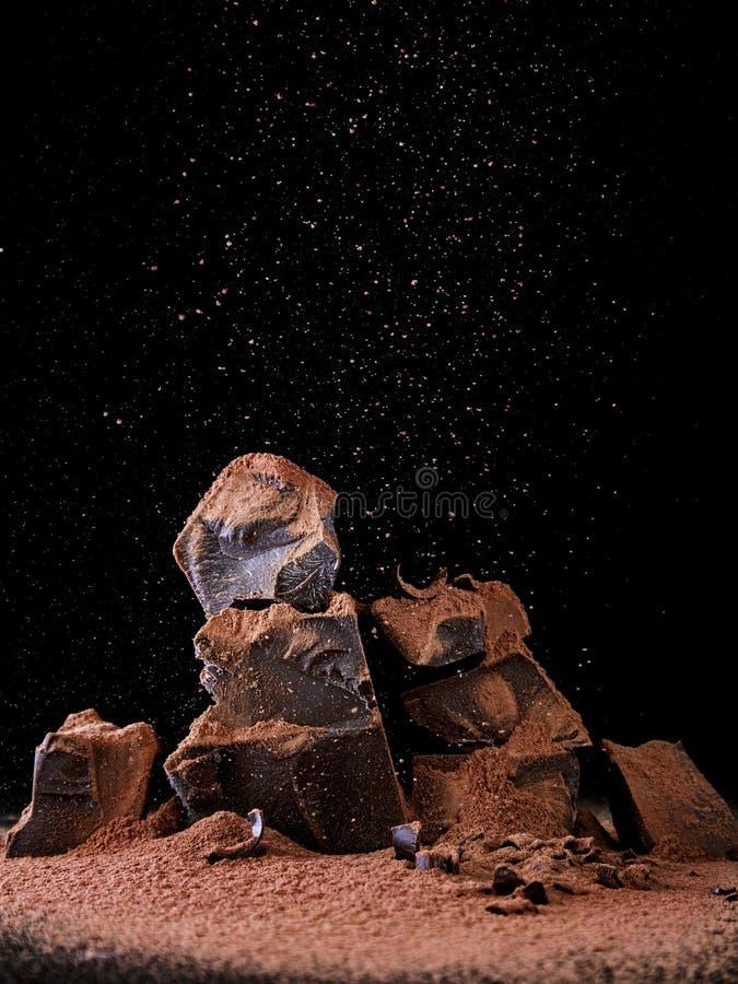 Il cioccolato ha fracassato i blocchi con cacao in polvere su fondo scuro fotografia stock
