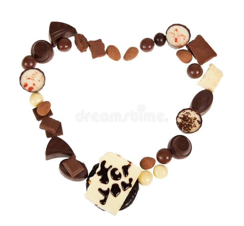 Il cioccolato, ordinato, caramelle della pralina, mandorle ha allineato nella forma del cuore, isolata su bianco fotografia stock libera da diritti