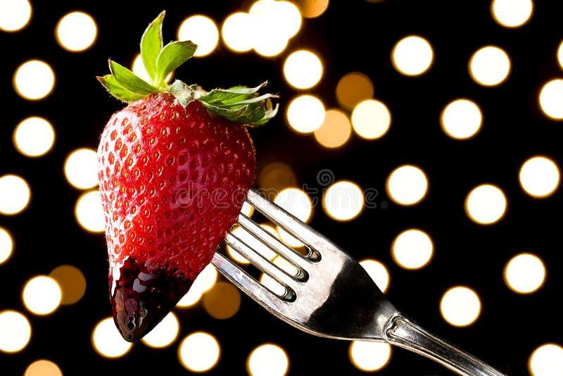 Il cioccolato romantico ha immerso la fragola su una forcella immagine stock