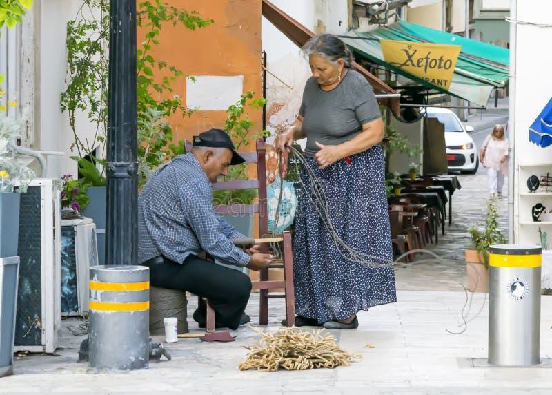 IL CIPRO, NICOSIA - 10 GIUGNO 2019: Coppie greche anziane degli artigiani che fanno le sedie di vimini su una via della città r f fotografie stock libere da diritti