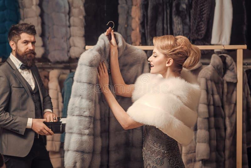 Il cliente con la barba e la donna comprano il cappotto simile a pelliccia immagini stock libere da diritti