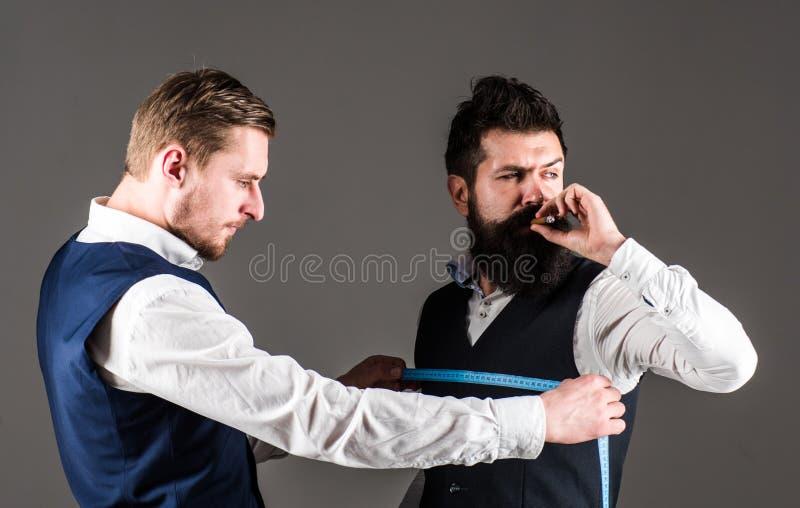 Il cliente con la barba ed il fronte rigoroso fumano il sigaro e la bevanda fotografie stock libere da diritti