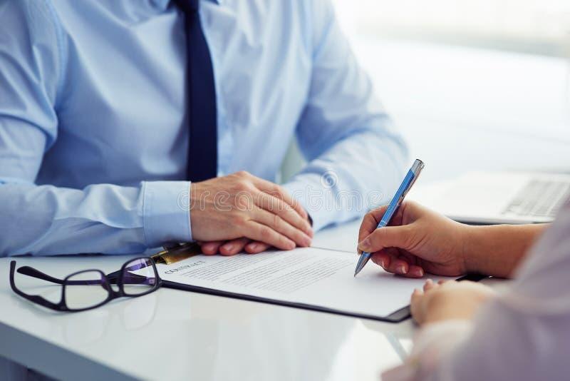 Il cliente femminile firma un contratto fotografia stock