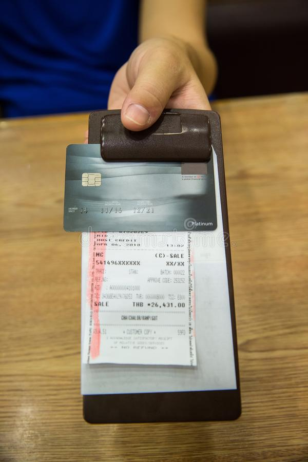 Il cliente ha passato la carta di credito sulla carta della fattura, nella ricevuta nera di cuoio della fattura fotografie stock libere da diritti
