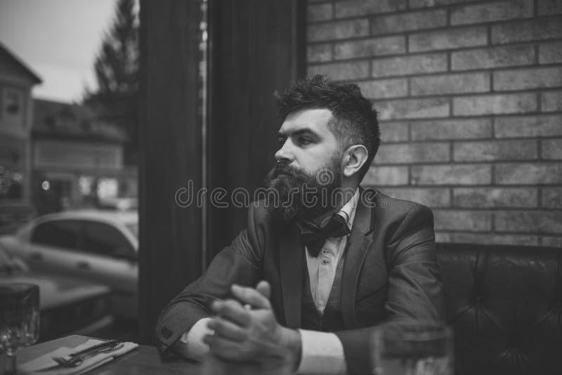 Il cliente sicuro della barra si siede in caffè e nel pensiero Riunione della data dei pantaloni a vita bassa che attende nel pub fotografia stock libera da diritti