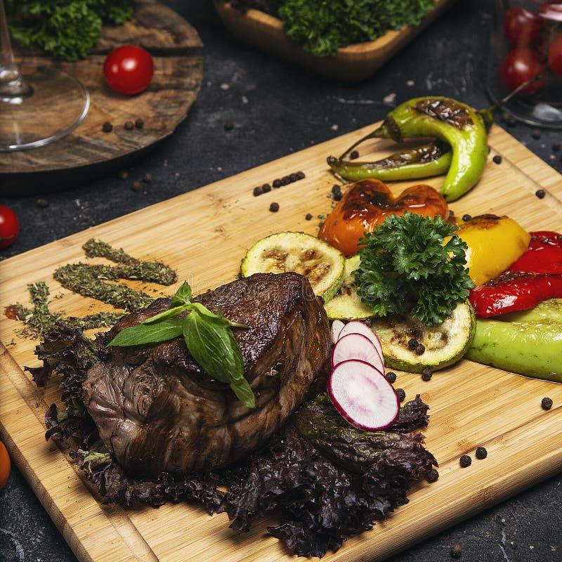 Il club rinforza la bistecca con e le verdure arrostite immagine stock