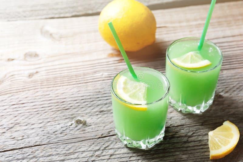 Il cocktail della margarita con il limone ed i cubetti di ghiaccio sulla vecchia tavola di legno fotografia stock libera da diritti
