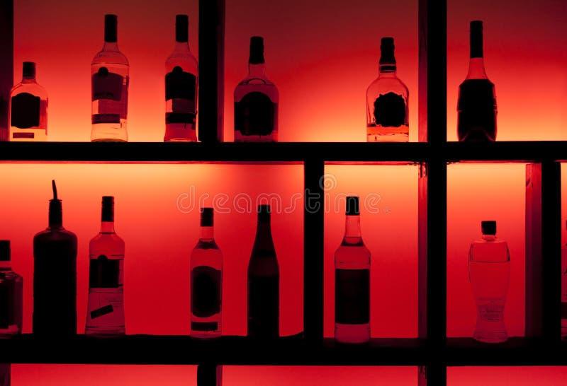 il cocktail posteriore delle bottiglie della barra si è illuminato immagini stock