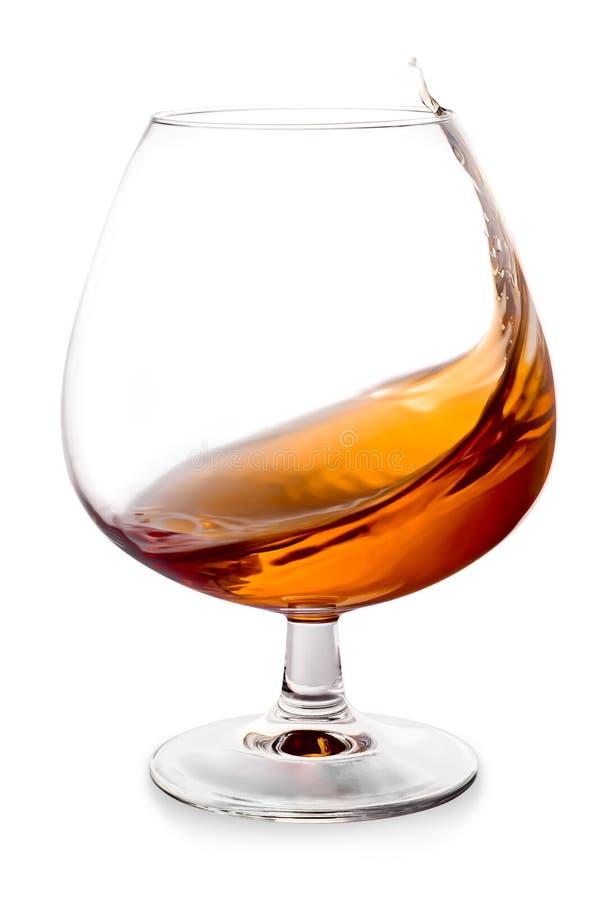 Il cognac spruzza in un vetro fotografie stock