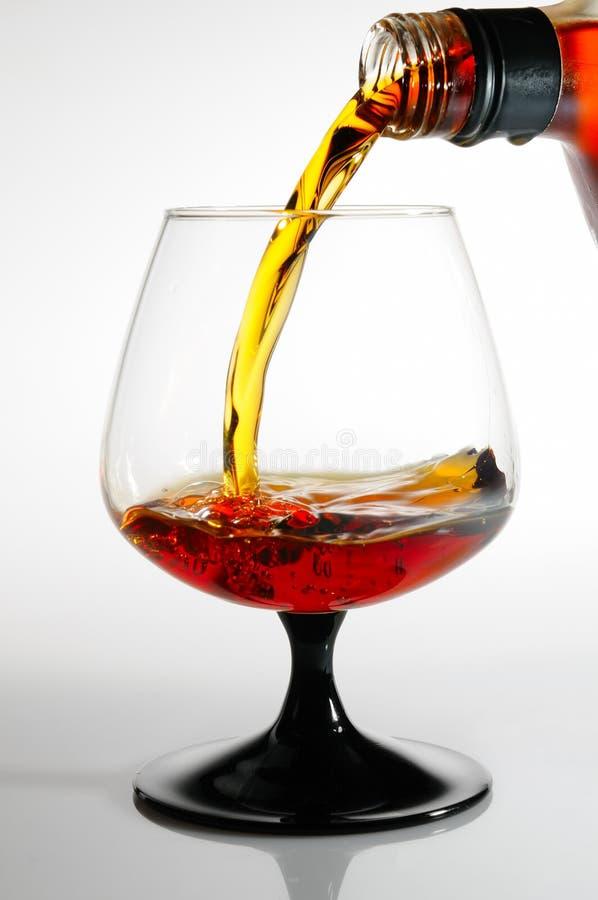 Il cognac versa da una bottiglia in un vetro fotografie stock