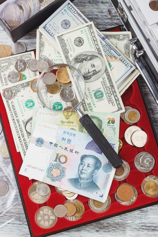 Il collettore differente conia nella scatola, nelle banconote e nella lente d'ingrandimento immagini stock